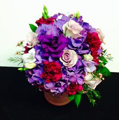 Purple hydrangeas, lavender roses, carns for a bridesmaid's bouquet www.bertholdsflowers.com