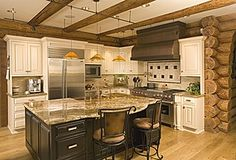 White glazed cabinets, beams, black stained island - in a log home. From Zillow Digs Rustic Kitchens