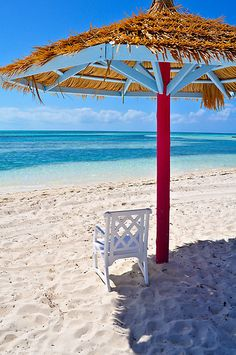 Coco Cay, Bahamas - a chair under a palapa and a view of gorgeous water.   Aspen Creek Travel - karen@aspencreektravel.com