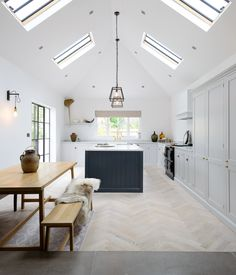 A beautifully big and bright deVOL Shaker kitchen painted in Damask and Pantry Blue with brass details and a lovely parquet floor.