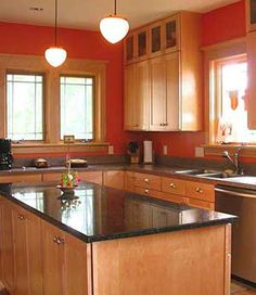 I like these shaker style cabinets with the black granite countertop.