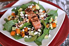 Salad with spinach, roasted butternut squash, cranberries, avocado, feta and almonds topped with leftover maple soy salmon and dressed with balsamic and lime honey ginger infused olive oil