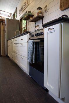 White kitchen cabinets, granite countertop, full-sized stove and refrigerator.