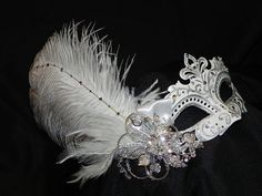 White and silver masquerade mask with feathers and a crystal flower cluster