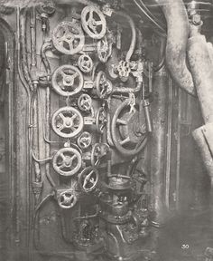 This photograph shows the U-Boat 110, a German Submarine that was sunk and risen in 1918. This photograph shows the Control Room looking forward to port side, showing the Submarine's valve wheels to high pressure air system and the reducing valves for air temperature.