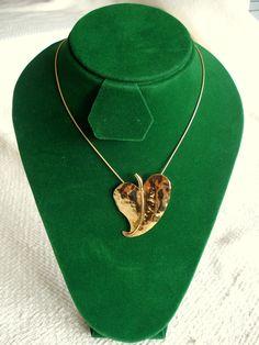Dije Hoja Corazón, elaborado en cobre tallado bañado en oro, montado en cuero. Rubén Riera - Otras piezas en: www.facebook.com/...