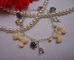 Armkettchen mit beigefarbenen Schleifen, kleinen silbernen Perlen und Metallanhängern