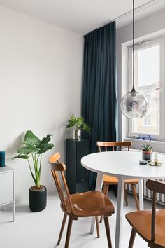 Monochrome dining area with some wooden vintage chairs, a round white table, a modern pendant light, green plants and dark blue curtains. We love this modern and minimal look! Check out the whole makeover on our website! Dark Blue Curtains, Dining Area, Dining Chairs, Modern Pendant Light, Vintage Chairs, Studio Apartment, Small Apartments, Designer, Minimalism