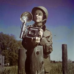 Sergeant Karen Hermiston of the Second World War Canadian Women's Army Corps holding a speed graphic camera, circa 1944 ~