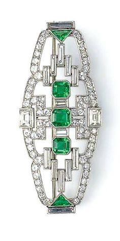 AN ART DECO EMERALD AND DIAMOND BROOCH, BY DREICER & CO.  Designed as a circular and old European-cut diamond openwork tapered panel, set with three central cut-cornered square-cut emeralds, spaced by rectangular-cut diamonds, extending baguette and square-cut diamond and triangular-cut emerald detail, mounted in platinum, circa 1925 Signed Dreicer & Co.