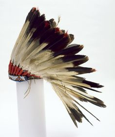 Cheyenne Eagle feather bonnet with a leather cap, red white and yellow beaded band, and red wool wraps around the feathers.ca. 1885-1895