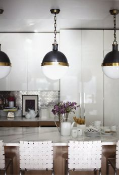 Kitchen: Glossy cabinets, light fixtures, marble.