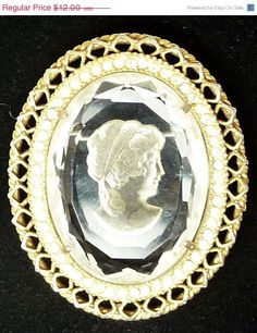Reverse Intaglio Cameo Brooch - Vintage Carved Style Pin offered by TheJewelSeeker  This brooch reminds us of the Whiting and Davis made very similar to this one. This one is made of glass, and is carved or molded from the back side, making the front smooth and flat and faceted around the oval edges. The cameo is prong set in a goldtone frame with rhinestones around teh inside edge and a webbed metal frame. The hinged pin stem is built in with a c style safety mechanism.   Style: Cameo Pin…
