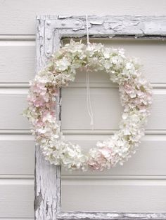 Hydrangea wreath hanging from a shabby frame.
