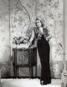 """Hand-painted wallpaper was the epitome of elegance and fashion in 1930s Hollywood. """"Decorator to the stars"""", William Haines used a Chinese wallpaper panel as a backdrop for this portrait of actress Constance Bennett."""