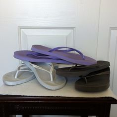 Gap Flip Flops Size Ten Three pairs of flip flops: 1.  Gap - white with silver trim. Barely worn.  2. Gap - black/charcoal grey. Barely worn but a small tear in bottom of left heel (see picture).  Not marked, but they are from Gap.  3. Gap - purple. Barely worn. Not marked, but they are from Gap.  Will sell separately or choose your own colors. See other listing for other colors.  (35) GAP Shoes Sandals