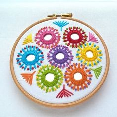 This bright and colourful hoop has been hand embroidered using my own design onto a background of crisp white cotton. The design incorporates seven small mirrors which have been individually and securely stitched in place (a technique known as shisha . Embroidery On Kurtis, Hand Embroidery Videos, Hand Embroidery Tutorial, Hand Embroidery Flowers, Embroidery Works, Creative Embroidery, Hand Embroidery Stitches, Hand Embroidery Designs, Beaded Embroidery