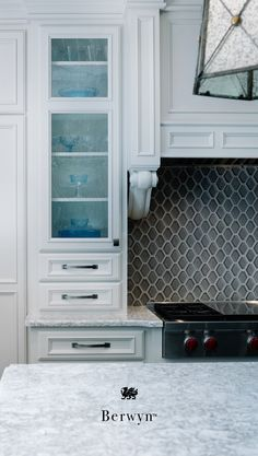 Cambria Berwyn combines cream, taupe, and varying grays for a quartz countertop that is more durable and stain-resistant than granite countertops. This granite alternative has a slight shimmer and intricate movement. White cabinets, gray hexagon backsplash, and Berwyn pair for a luxurious, low-maintenance white and gray kitchen. #MyCambria