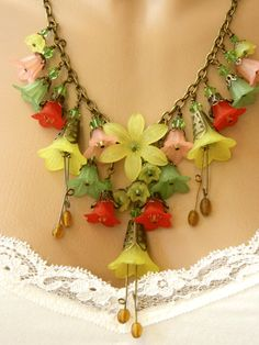 This statement Lucite flower and crystal necklace is as colorful as a spring bokay The lovely trumpet flowers bell flowers and other flowers in yellow red green and peach are