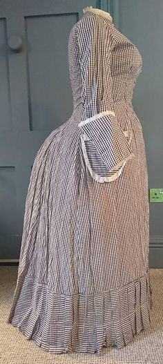 A very interesting dress, this is one of those rare survivors - a piece of everyday workwear, in superb condition and possibly with a tale to tell ?? The dress dates to the late 1870s / early 1880s natural form bustle era - the design nods to the fashionable silhouette of the