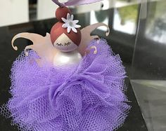 Good Fortune Fairy  This is my unique take on the popular pompom doll. It has been handcrafted to the highest standards. She is approx. 12cm tall and comes in a clear presentation box. She can be kept in the box or has a hanging loop of approx 15cm so she can be hung.  It is an ideal gift for a newborn baby to bring good fortune, but is also fab as a christening gift.  It is a beautiful gift to a bride or from the bride to her bridesmaids.  This item is for home decor only and not suitable…