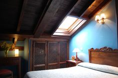 Habitación abuhardillada con cama de matrimonio.