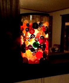 Button lamp, buttons between two glass containers and candle in the middle one.