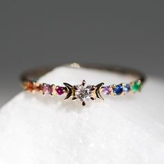Rainbow colored, just like the cosmos. What a unique engagement ring. I love this. This would also be cool for LGBT+ peeps.
