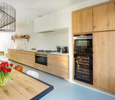 Op maat gemaakte Fred constant keuken van eiken, solid surface en staal. Mooi hoe de hoge kasten en de afzuigunit zijn geïntegreerd in het stucwerk. De apparatuur is van Siemens en Pitt-Cooking.