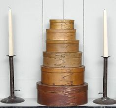 """Stack of six oval boxes: maple, pine and oak, three and four-finger graduated sizes, largest in original red painted finish, 3 3/4"""" h, 10"""" l; next to largest in original ochre stain, 3 1/2"""" h, 8 3/4"""" l; remaining four boxes in natural finish, 2 3/4"""" h, 7 3/4"""" l; 2 1/4"""" h, 6 1/2"""" l; 2"""" h, 5 3/4"""" l; 1 3/4"""" h, 4 3/4"""" l. Also, a pair of candlesticks, rolled sheet iron, hogscrape style, tall shafts, with sliding thumb latch to extract candles, circular bases, 9 1/4"""" h, 5"""" dia bases. The Doug…"""