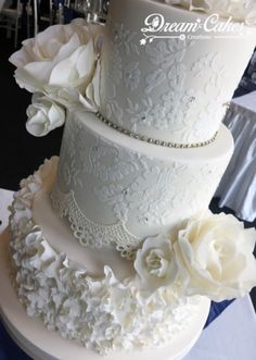All white wedding cake. Edible sugar flowers and lace with ruffles