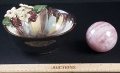 NICE LOT INCLUDES A LOVELY HEAVILY GLAZED BOWL WITH DRIPPED COLORING AND APPLIED FLOWERS. MARKED HAND MADE IN AUSTRIA. MEASURES 3 INCHES TALL AND 7 INCHES IN DIAMETER. THIS REDWARE BOWL HAS A VERY SHALLOW CHIP ON THE BASE. INCLUDES A SOLID POLISHED AMETHYST COLORED STONE PAPERWEIGHT BALL.
