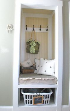 Small closet converted into mudroom bench, coat rack, and shoe storage area.
