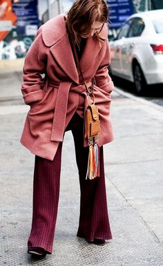 Courtney Trop wears a mauve long wool coat, a burgundy ribbed top and matching pants, velvet pumps, and a Chloé mini fringed bag