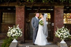 Floral arrangements made of roses, dahlias, delphinium, salal, ranunculus,and mint greet guests at the reception doors. Wedding Flowers: Seasonal Celebrations.