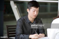 ストックフォト : Young man is signing document