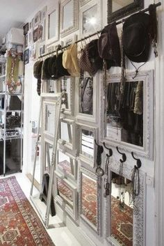 Accessory storage mixed within a very cool wall design hanging hats scarves and long necklaces against a backdrop of framed mirrors