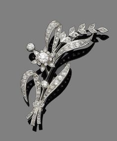A diamond spray brooch  Modelled as a flower, set throughout with old brilliant, single and rose-cut diamonds, principal diamond approx. 0.70ct total, remaining diamonds approx. 1.65cts total, length 7.5cm