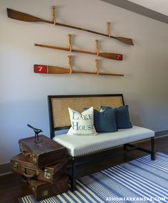 Lake house entryway with rope hung vintage boat oars over a Noir Colonial Caning Hand Rubbed Black Bench accented with blue velvet pillows and a Lake House print pillow with stacked vintage suitcases to the left atop a striped blue and white rug layered over hardwood floors.