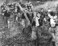 """Lumber Jills"" of the Women's Timber Corps.  While the Land Girls harvested crops, the Lumber Jills harvested timber. For the most part, their uniforms were identical to the Land Girls, with the exception of their headgear (green berets instead of brown hats) and their branch specific badge."