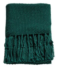 Dark green. Throw in soft, moss-knit fabric with wool content. Fringe at short sides.