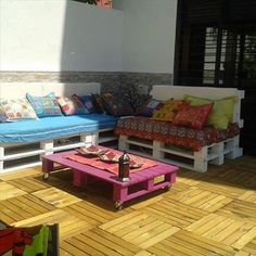 In this picture a beautifully painted wooden pallet table is shown which is placed on the sunny place where sunlight is glowing.