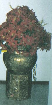 Grande arranjo natalino de chão, com base em madeira oitavada revestida com metalização envelhecida, o mesmo trabalho feito no grande vaso de cerâmica, com o gargalo enfeitado de fitas aramadas diversas, bolas e sinos.  Arranjo floral com bicos de papagaio vermelho foscos e maços de trigo natural. Altura do arranjo, 1,2 metro. Elo7 - Mimos da Zelia.