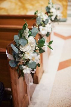 cathedral is set for the wedding with pew markers of white roses, white tulips, white larkspur, button camomile and eucalyptus greenery tied with cream satin ribbon to mark the family rows.
