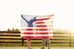 Silhouette kiss behind the American flag-military-Fourth of July engagement session