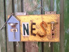 "Feather Your Nest with this hardware ""Nest"" sign.Sign is made from salvaged hardware,license plate letters, barn wood and three hooks along the bottom for keys. Junk Chic 5280"