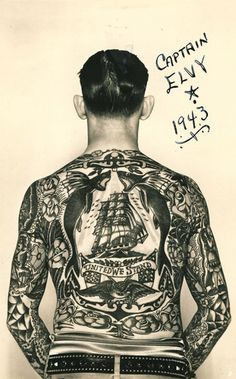 """""""Captain Elvy"""" and his """"full body suit""""  of tattoos. Elvy's back features a clipper ship,  roses, flying fish, eagle, American flags, and a  banner reading """"United We Stand."""" c. 1940.  (Courtesy Tattoo Archive, Winston-Salem, NC)"""