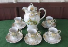 "Antique Leuchtenburg Germany chocolate / tea set with 5 cups and saucers floral pattern beaded handle with gold spray gold trim though it has faded in spots gold fern design approximately 9"" tall to top of teapot finial tiny cups are 3"" tall saucers are 5"" acrossAsk questions..I will reply."