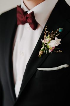 Mahogany bow tie with a colorful boutonnière. It adds a rustic style to the outfit.