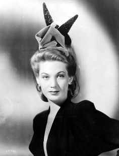 1945 Louise Allbritton wears a Madame Satan chapeau of American beauty velvet with two horn-shaped black feathers sprinkled with black sequins